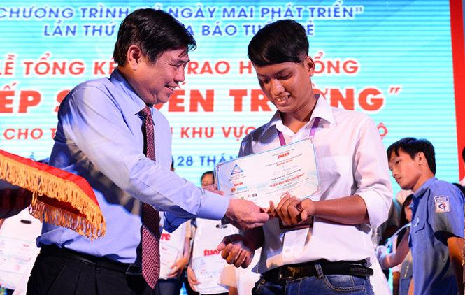 Ông Nguyễn Thành Phong, phó bí thư Thành uỷ TP.HCM, trao học bổng cho các tân sinh viên vượt khó